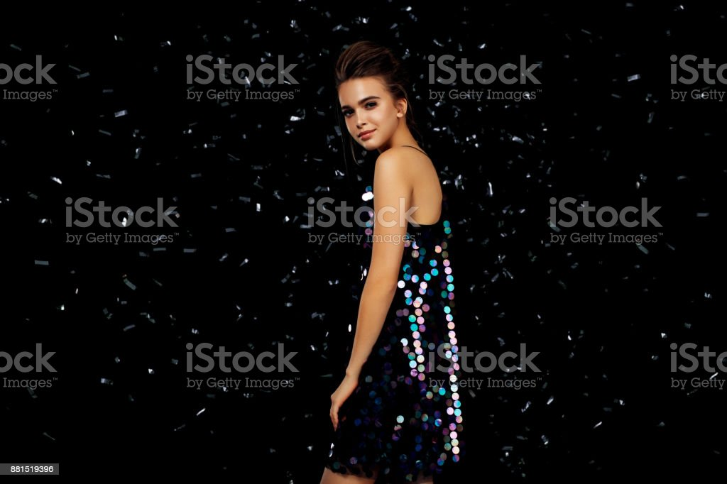 Woman dancing on a party over black background with confetti stock photo