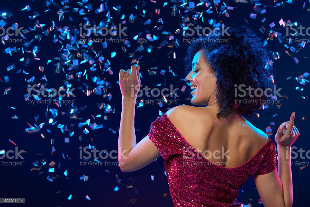 Woman dancing on a party over colorful background with confetti – Foto