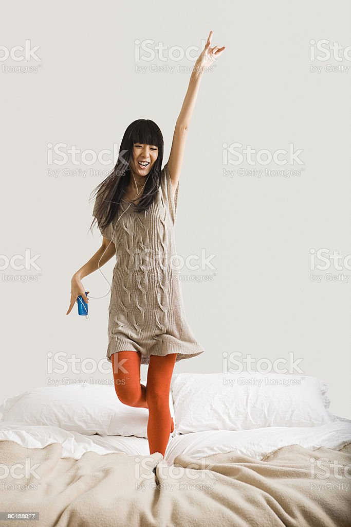 Woman dancing on bed stock photo