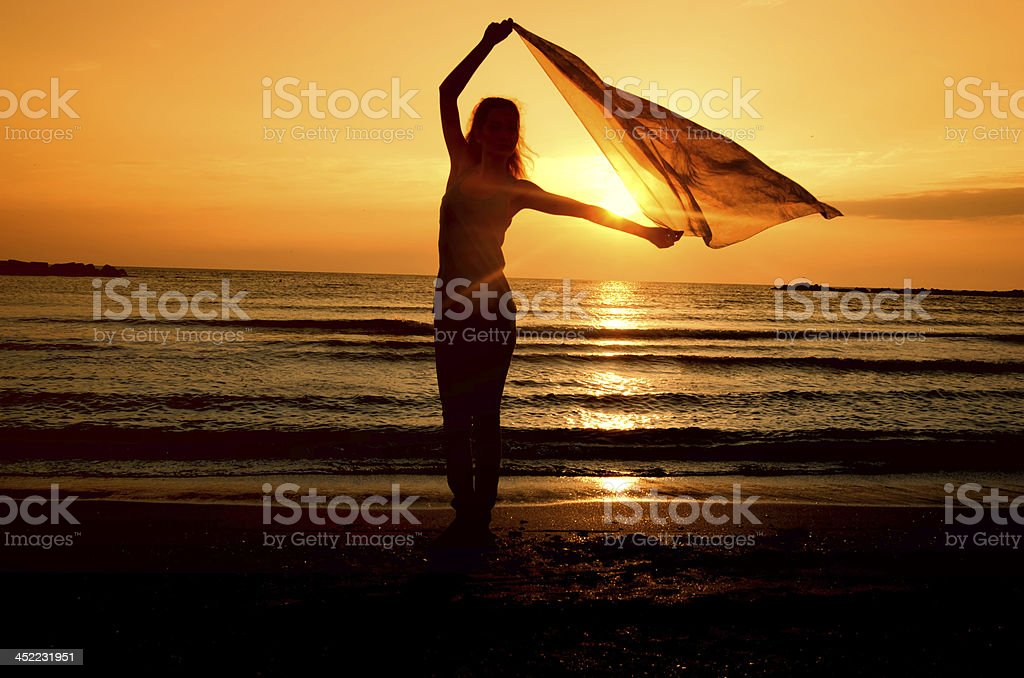 Woman dancing on the beach at sunrise stock photo