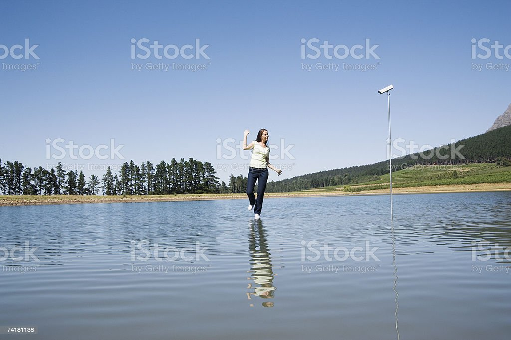 Woman dancing on water with surveillance camera and trees royalty-free stock photo