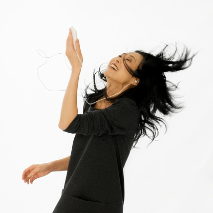 Asian woman flips back her hair while dancing to music from a portable player. Isolated on white.