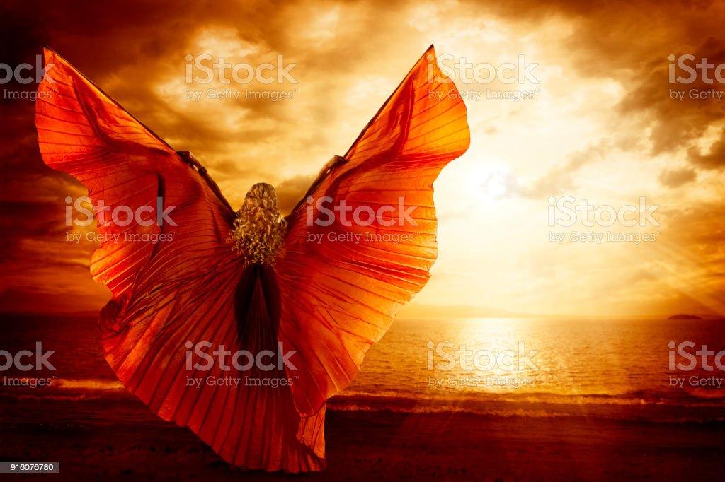 Woman Dancing Wings Dress, Fashion Art Model Flying on Ocean Sky Sunset stock photo