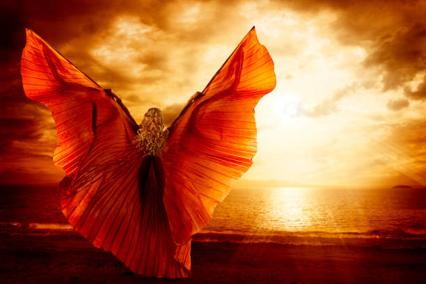 Woman Dancing Wings Dress, Fashion Art Model Flying on Ocean Sky Sunset stock photo