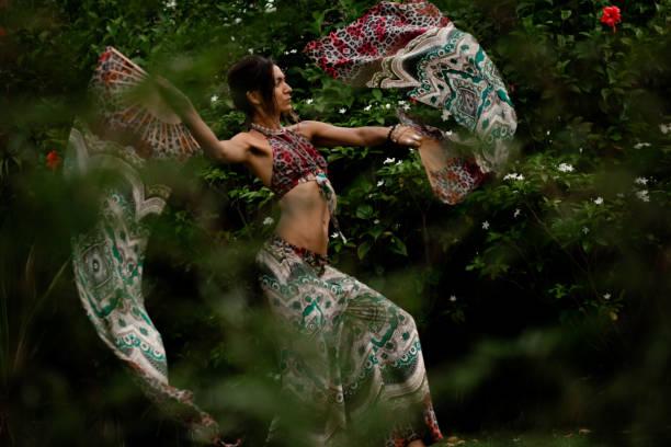 frau tanzt mit fans auf natürlichem tropischen hintergrund - hippie kostüm damen stock-fotos und bilder
