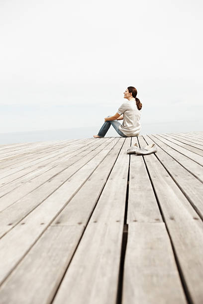 Woman day dreaming while sitting on a pier stock photo