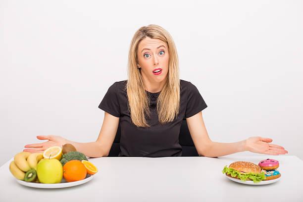 frau entscheidung zwischen gesunden und ungesunden lebensstil - gewicht schnell verlieren stock-fotos und bilder