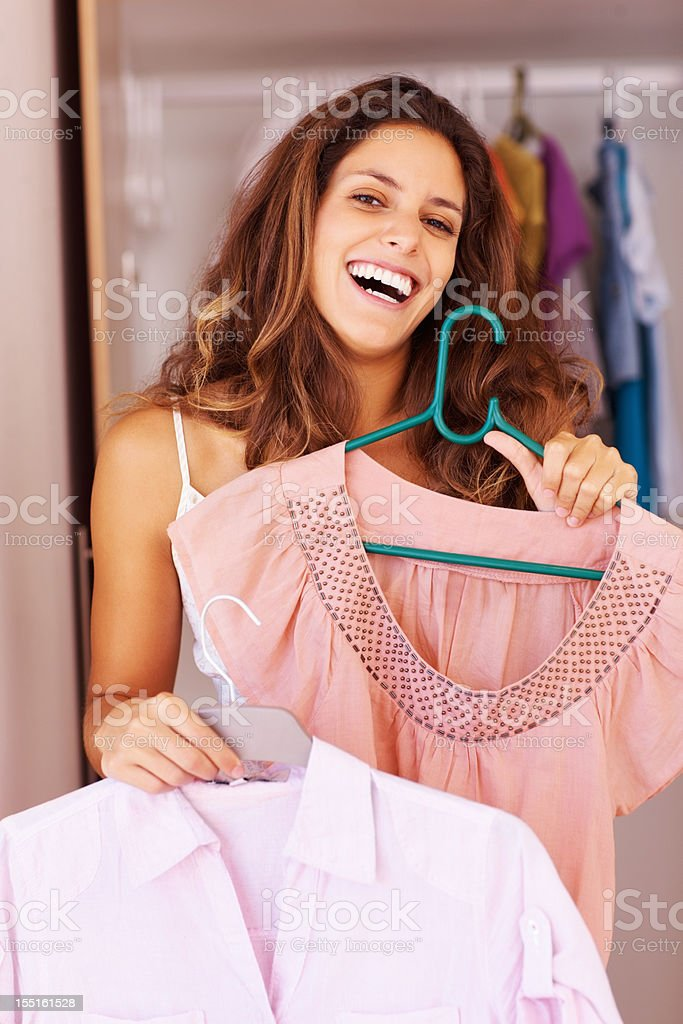 Woman deciding which dress to wear royalty-free stock photo