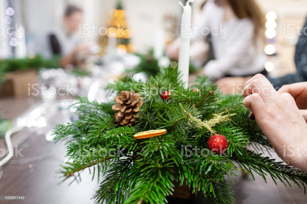 A Christmas Arrangement.A Woman Decorates A Christmas Arrangement With Candles Hands