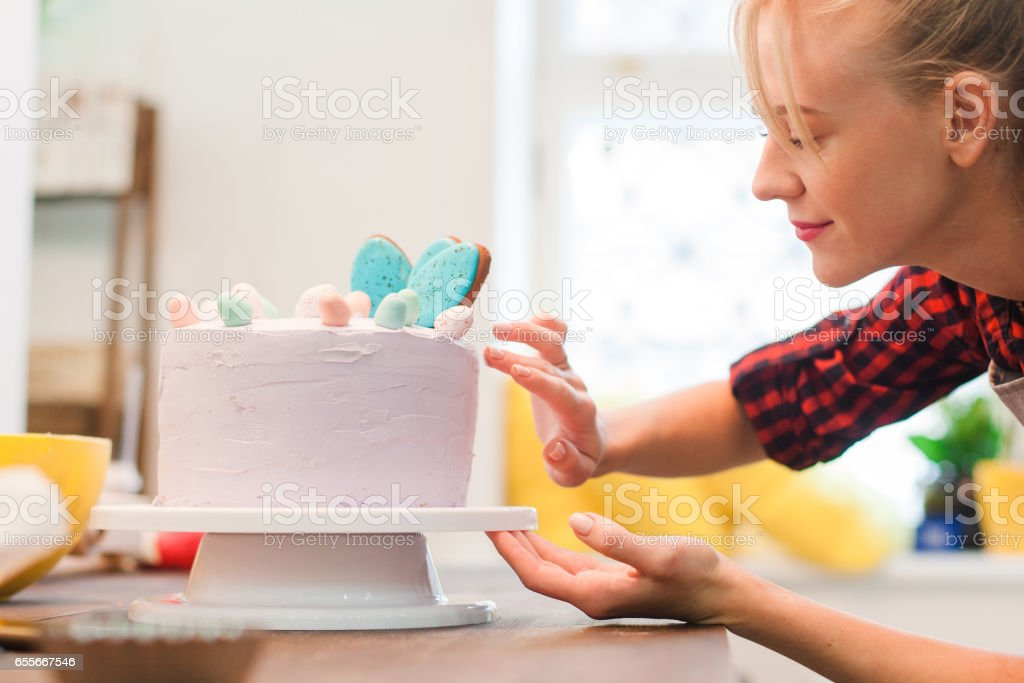 Woman decorates homemade cake. Culinary business. stock photo