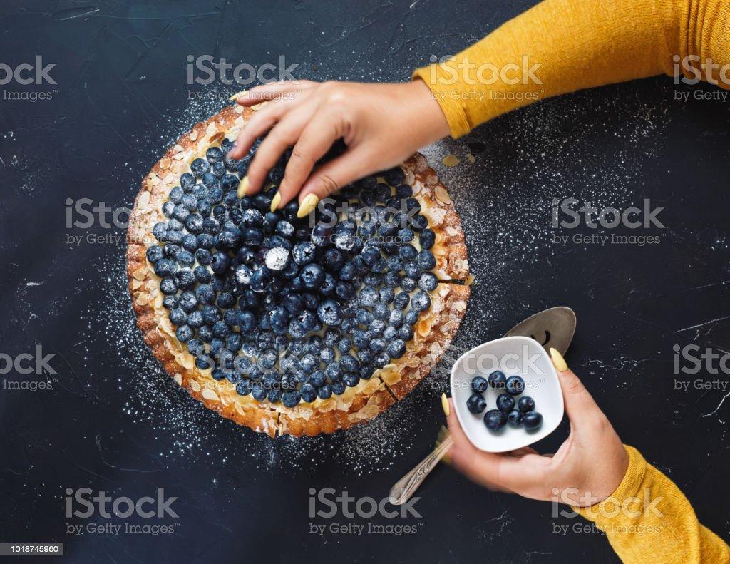 Mujer de decorar una tarta de arándanos - foto de stock
