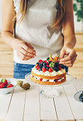 Woman decorating a cake with fresh berries and physalis