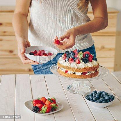 Woman placing raspberries on a cake