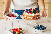 Woman decorating a sponge layer cake with fresh berries