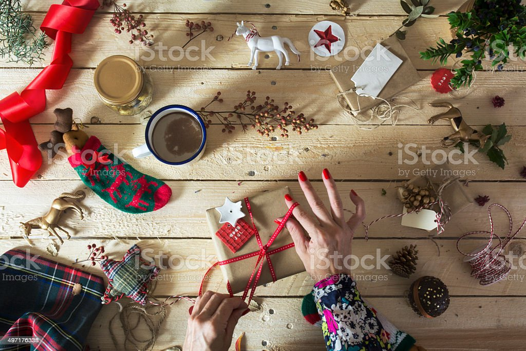 Woman decorating a Christmas present, surrounded by festive deco stock photo