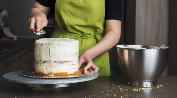 Woman decorating a delicious layered sponge cake with icing cream Unrecognisable woman decorating a delicious layered sponge cake with icing cream decorating a cake stock pictures, royalty-free photos & images