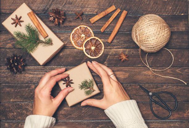 Frau Weihnachtsgeschenke zu verzieren. Geschenke Verpacken Inspirationen. Hände, Geschenkboxen, Kugel aus Jute, Zimtstangen, Anis, Orangenscheiben, Fer Äste und Retro-Schere auf rustikalen hölzernen Hintergrund. – Foto