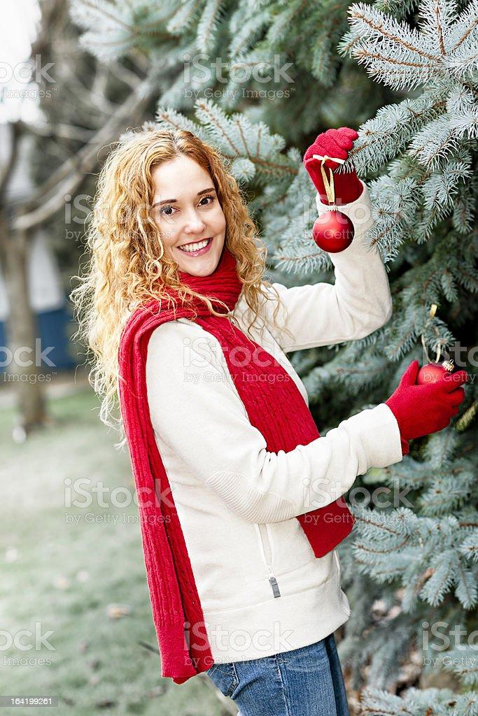 Woman decorating Christmas tree outside royalty-free stock photo