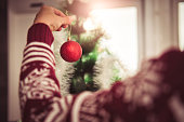 Woman wearing red sweater holding red ornament and decorating christmas tree