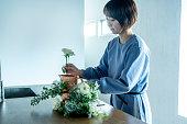 自宅で花を飾る女性