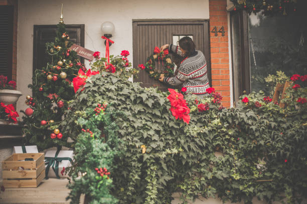frau, die vordere tür mit adventskranz dekorieren - deko hauseingang weihnachten stock-fotos und bilder