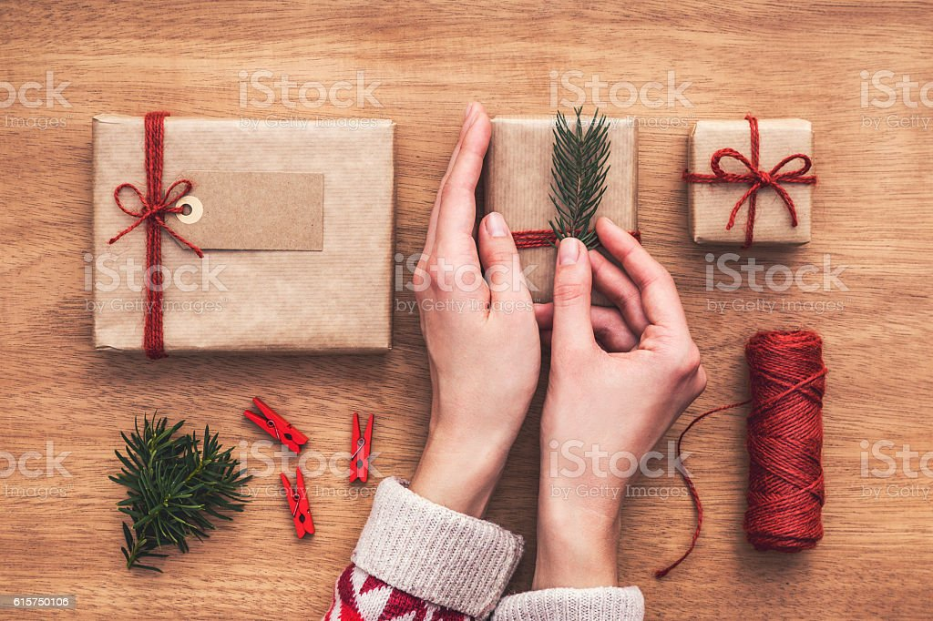 Woman decorating gift boxes with small, green twig. Hands close stock photo