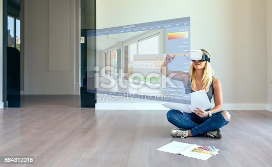 istock Woman decorating with virtual reality glasses 864312018