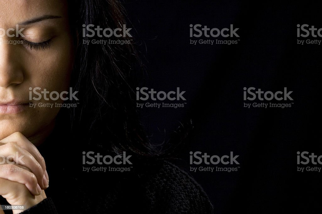 A woman deep in prayer and a black background stock photo