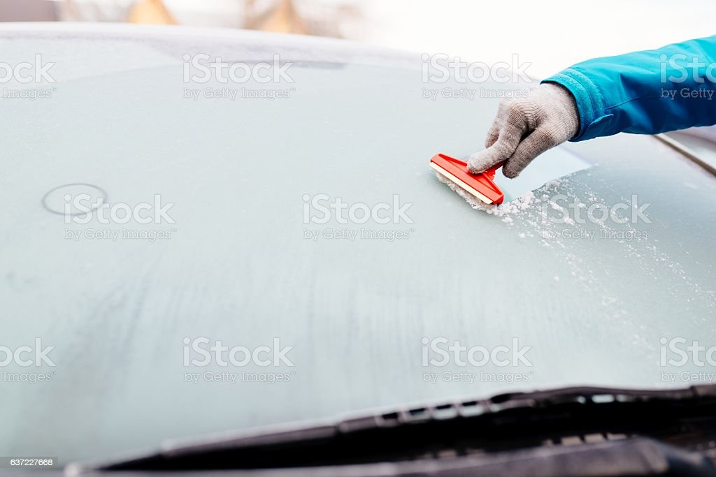 Woman deicing front car windshield with scraper stock photo