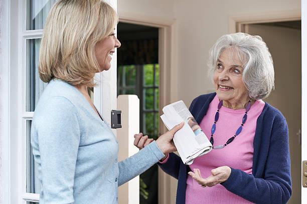 woman delivering newspaper to elderly neighbour - einen gefallen tun stock-fotos und bilder