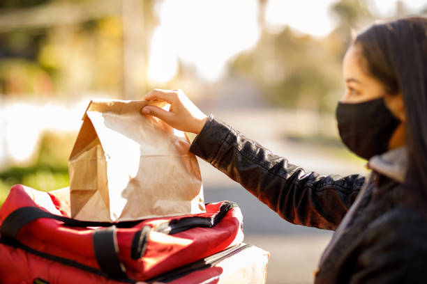 Woman delivering package- Motogirl, Motoboy stock photo