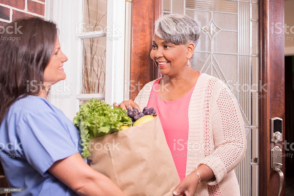 Woman delivers groceries to senior adult woman at home. stock photo