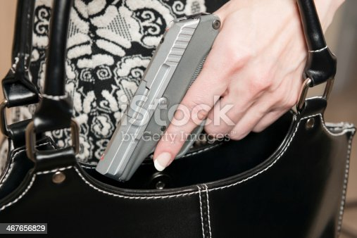 A female hand pulling a small caliber handgun out of a black purse.