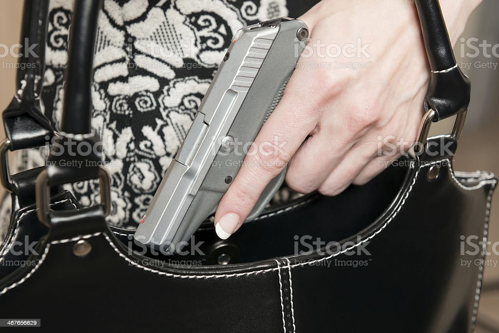 Woman demonstrating a concealed weapon stock photo