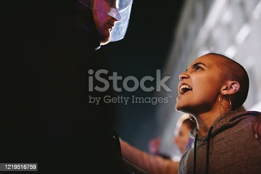 Angry female protestor giving slogans in front of police force. Woman demonstrating against police violence at night.