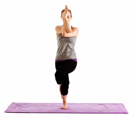 woman demonstrating garudasana or eagle pose yoga pose on