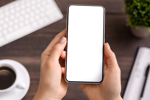 Woman demonstrating modern smartphone with blank white screen