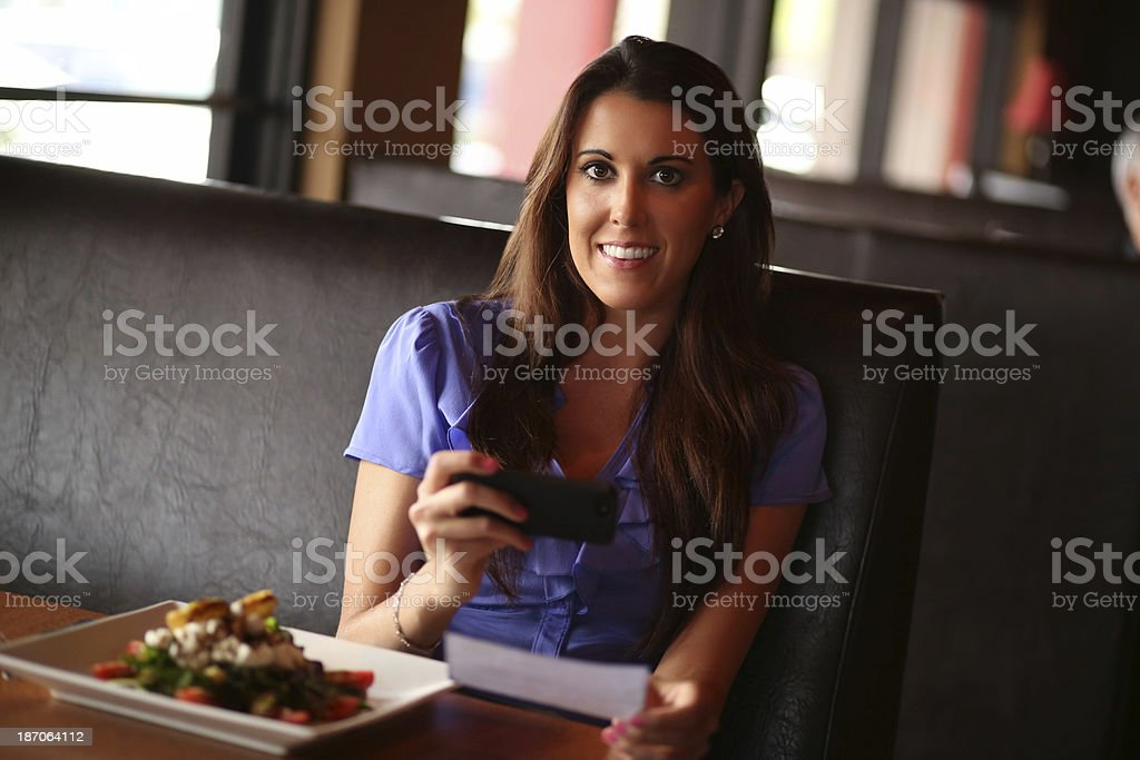 Portrait of beautiful mature woman depositing check through mobile...