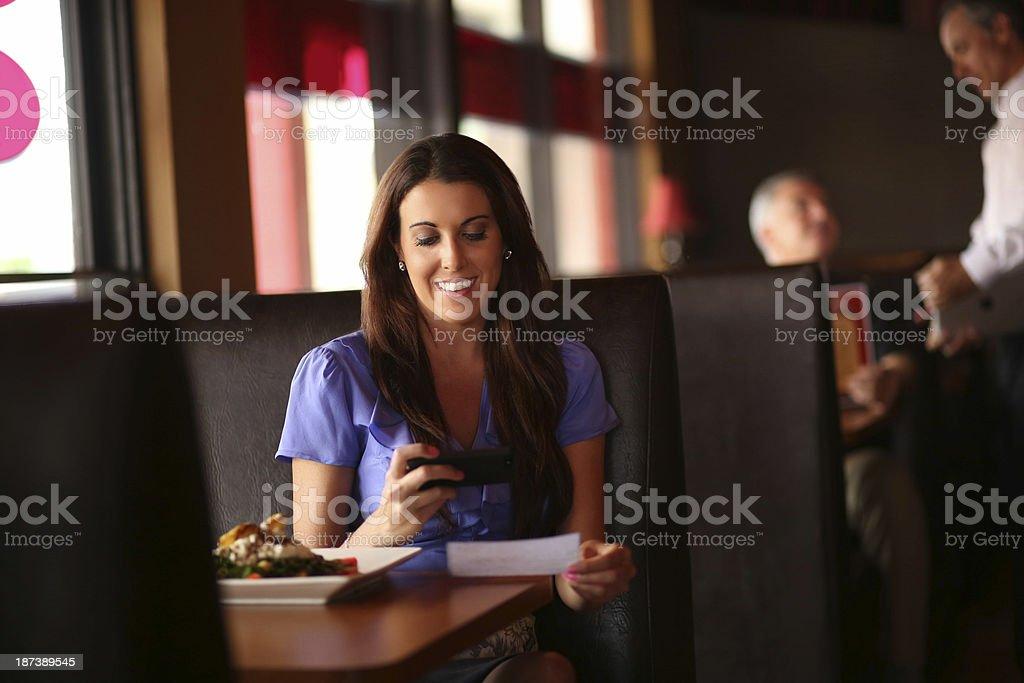 Beautiful mature woman depositing bank check through mobile phone at...