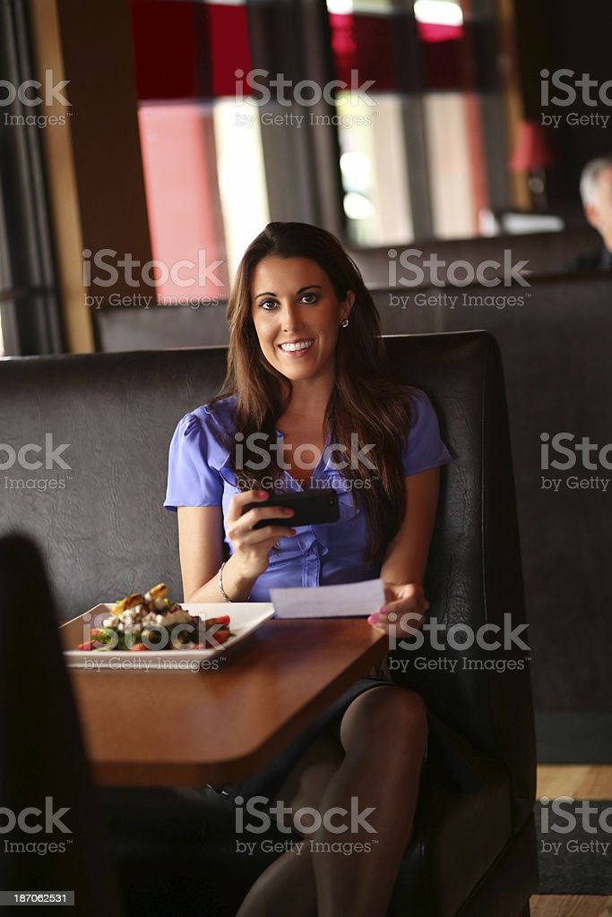 Portrait of beautiful mature woman depositing check through smart...