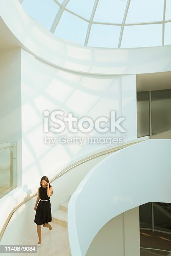Young Chinese woman descending walking exploring exploration discovery admiration awe wonder curiosity staircase stairs marble banister design interior modern contemporary architectural architecture building with skylight window looking forward in admiration