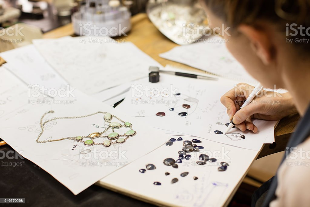 Woman designer makes and design jewelry in workshop - Photo