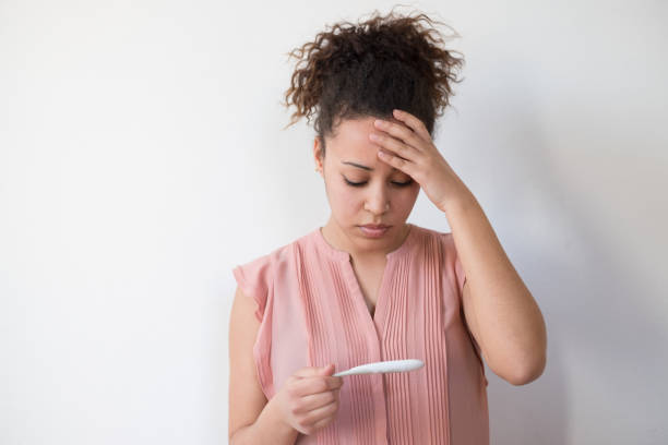 Woman desperate after reading pregnancy test result stock photo