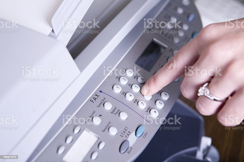 Woman dialing a number to send a fax stock photo
