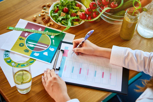 woman dietitian in medical uniform with tape measure working on a diet plan sitting with different healthy food ingredients in the green office on background. weight loss and right nutrition concept - dietician stock pictures, royalty-free photos & images