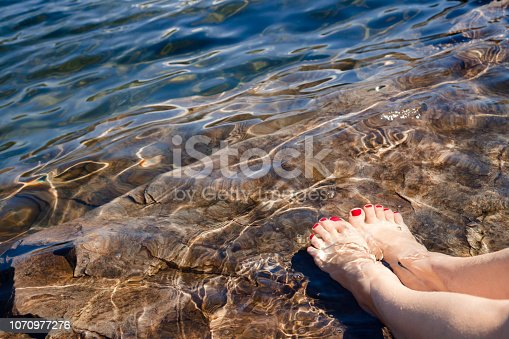istock Woman dipping her feet in a crystal clear water of a lake in Norway 1070977276