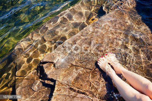 522909925 istock photo Woman dipping her feet in a crystal clear water of a lake in Norway 1070977286