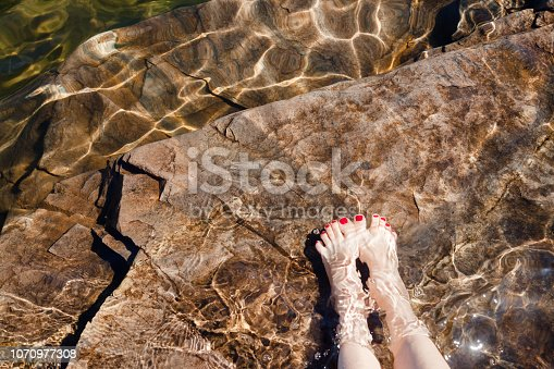 522909925 istock photo Woman dipping her feet in a crystal clear water of a lake in Norway 1070977308