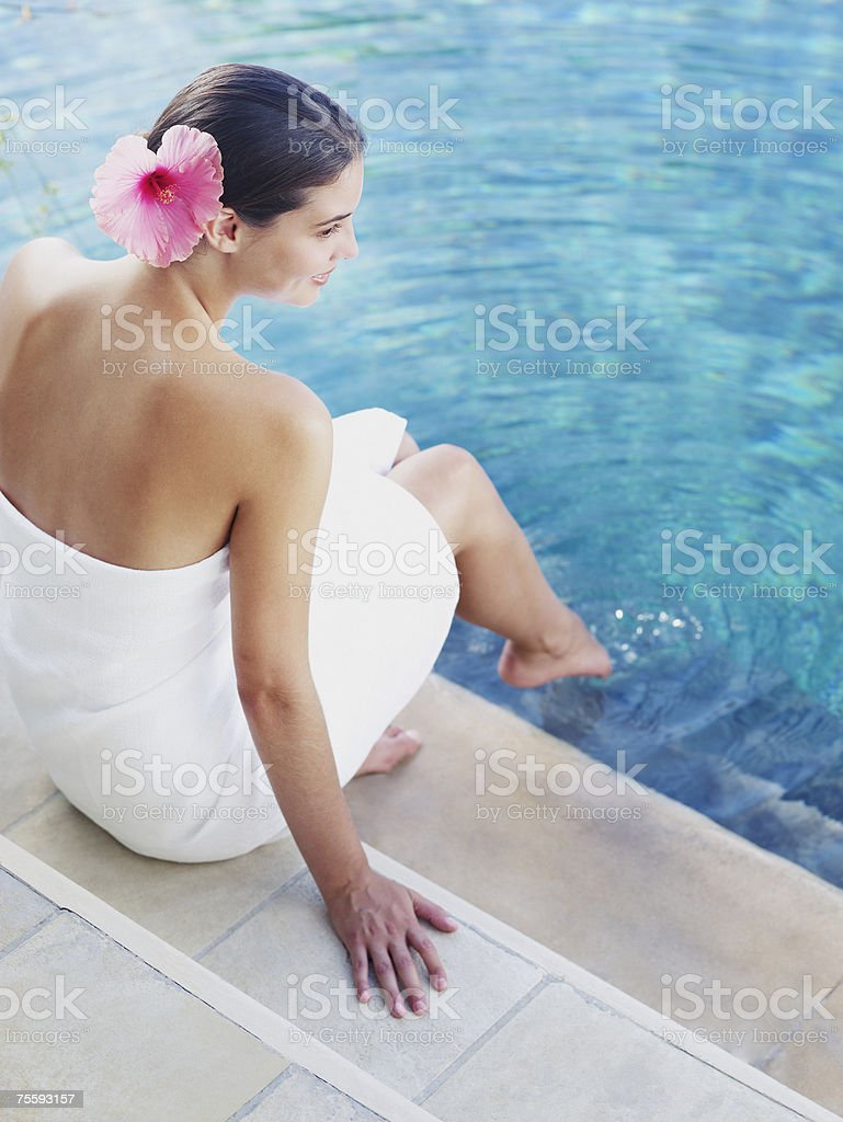 Woman dipping her toes in a pool with a white towel around her royalty-free stock photo