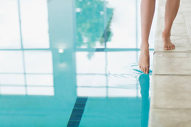 Woman dipping toe in swimming pool stock photo